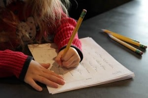 Child's Hands Doing Worksheets with Pencil